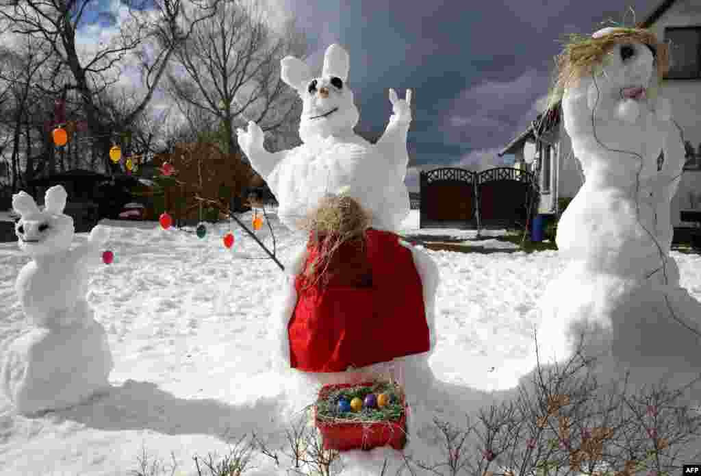 An Easter Bunny made out of snow is pictured on the side of the road to advertise rooms for rent in Ahrenshoop, Germany.
