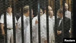 FILE - Ousted former Egyptian president Mohamed Mursi (R) speaks with other senior figures of the Muslim Brotherhood in a cage in a courthouse on the first day of his trial, in Cairo, Nov. 4, 2013.