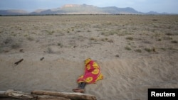 FILE - A Turkana man sleeps on the western shore of Lake Turkana close to Todonyang near the Kenya-Ethiopia border in northern Kenya, Sept. 25, 2014.