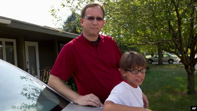 Lowell Highby and his adopted son, Alex, pose in front of their hom in Iowa, Jul. 10, 2012.