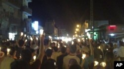 In this citizen journalism image made on a mobile phone Tuesday May 10, 2011 and acquired by the AP, Syrian anti-government protesters carry candles during a rally in the northeastern city of Qamishli, Syria. Syrian activists and eyewitnesses said on Wedn