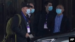 Members of the WHO team including Peter Daszak, left, Ken Maeda, right, and Vladimir Dedkov, second right, prepare to leave for a fourth day of field visits from their hotel in Wuhan in central China's Hubei province on Monday, Feb. 1, 2021. (AP Photo/Ng Han Guan)