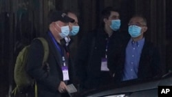 FILE - Members of the World Health Organization team including Peter Daszak, left, Ken Maeda, right, and Vladimir Dedkov, second right, prepare to leave for field visits from their hotel in Wuhan in central China's Hubei province.