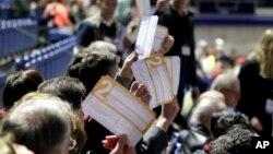 Para peserta Kaukus di bagian tempat duduk untuk kandidat capres dari Demokrat, Joe Biden, mengacungkan surat suara, di Knapp Center, Des Moines, Iowa, 3 Februari 2020.