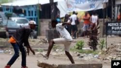 Des manifestants brisent des rocs pour ériger une barrière à Kinshasa, 19 septembre 2016.