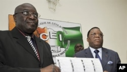 Director of Ivory Coast's Prime Minister Soro's Cabinet Paul Koffi (L) and president of Ivory Coast's Independent Electoral Commission (CEI) Youssouf Bakayoko (R) present the new provisional electoral list ahead of national elections in Abidjan, 12 Jul 20