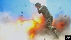 Borbena fotografkinja vojske SAD, specijalistkinja Hilda Klejton, snimila je ovu fotografiju 2. jula 2013, koju je objavila Vosjka SAD i na kojoj se vidi avganistanski vojnik okružen plamenom u trenutku nesrećne eksplozije minobacača tokom vežbe avganistanske vojske bojevom municijom. (Spc. Hilda Clayton/U.S. Army via AP)