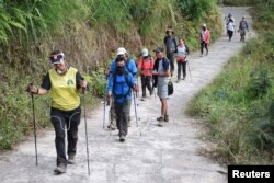 Para pendaki warga negara asing dan Indonesia berjalan di Desa Sembalun setelah turun dari Gunung Rinjani di Lombok Timur, 30 Juli 2018. (Foto: Akbar Nugroho Gumay/Antara Foto via Reuters)
