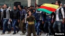 یک پسر کرد پرچم کردهای سوریه را بعد از پیروزی این نیروها در کوبانی در شهر حلب تکان می دهد.