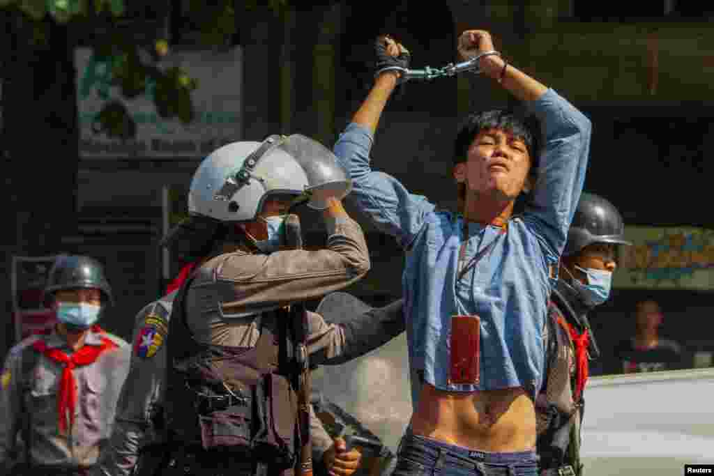 A pro-democracy protester is detained by riot police during a rally against the military coup in Yangon, Myanmar, Feb. 27, 2021.