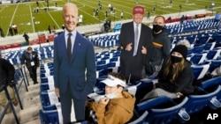 អ្នកទស្សនាការប្រកួតកីឡាបាល់ឱបរបស់អាមេរិក កាន់បដារូបបេក្ខជនប្រធានាធិបតីលោក Donald Trump និងលោក Joe Biden នៅទីក្រុង Provo រដ្ឋ Utah កាលពីថ្ងៃទី៣១ ខែតុលា ឆ្នាំ២០២០។