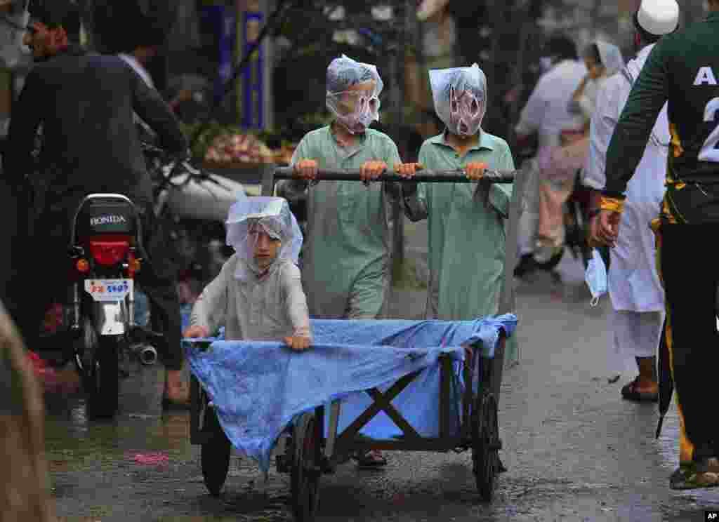 Pakistan, Peşəvarda yağış zamanı üzlərini plastik torba ilə örtmüş oğlanlar araba sürür.
