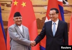 中國國務院總理李克強與來訪的尼泊爾總理奧利在人民大會堂簽字儀式上握手(2018年6月21日)