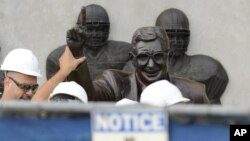 Trabajadores remueven la estatua del legendario entrenador de fútbol colegial universitario, Joe Patterno, el domingo, en el estadio de Penn State.