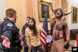 FILE - In this Jan. 6, 2021 file photo, supporters of Donald Trump, including Jacob Chansley, right with fur hat, are confronted by U.S. Capitol Police officers outside the Senate Chamber inside the Capitol in Washington.
