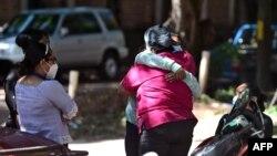 Familiares y amigos se abrazan mientras esperan los restos del periodista hondureño asesinado Luis Almendares, frente a la sede de la Junta de Medicina Forense en Comayagua, Honduras, el 28 de septiembre de 2020.
