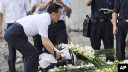 ນາຍົກລັດຖະມົນຕີຈີນທ່ານ Wen Jiabao ວາງຊໍ່ດອກໄມ້ ເພື່ອໄວ້ອາໄລໃຫ້ພວກເຄາະຮ້າຍຈາກອຸບັດຕິເຫດ ລົດໄຟຕຳກັນໃນສັບປະດາແລ້ວໃນເຂດເມືອງ Wenzhou ແຂວງ Zhejiang province (28 ກໍລະກົດ 2011)