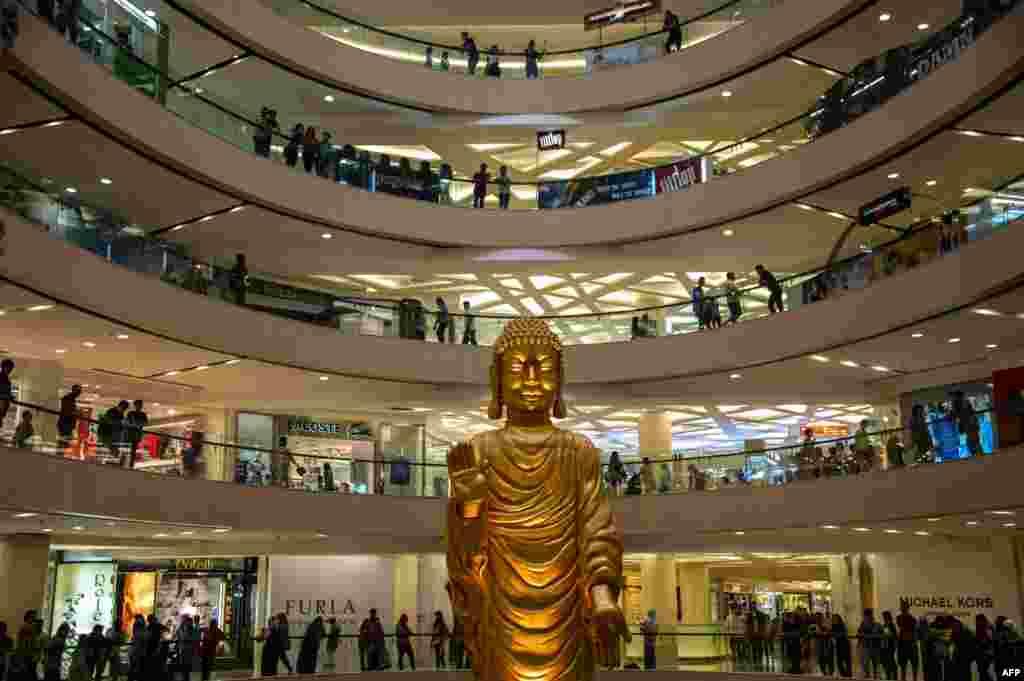 Patung Buddha raksasa dipasang di sebuah malll di Surabaya, Jawa Timur, Indonesia, tempat umat dan para pengunjung berdoa untuk merayakan ulang tahun Buddha.