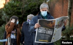 A man reads a newspaper as he waits to enter Lord's Cricket Ground to receive the coronavirus vaccine, in London, Britain, Jan. 22, 2021.