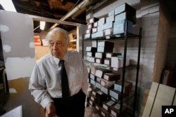 Peter Stefan, funeral director and proprietor of the Graham Putnam & Mahoney Funeral Parlor, stands in front of shelves holding the cremated remains of unclaimed bodies dating back more then a decade, in the basement of the Graham Putnam & Mahoney Funeral Parlor in Worcester, Massachusetts, Feb. 1, 2018.