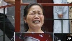 一名妇女2009年5月8日在北京卫生部前举着因食用毒奶粉而死亡的孙女照片,要求当局伸张正义。(资料照片)