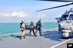 FILE - Royal Malaysian Navy personnel carry a body onto a U.S. Navy helicopter from USS America during a search and rescue operation for survivors of the USS John S. McCain.