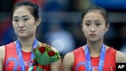 13일 중국 톈진에서 열린 동아시아경기대회 여자 체조 개인 도마 시상식에서 금메달을 차지한 북한의 홍은정 선수와 동메달의 리은하 선수가 나란히 서있다.