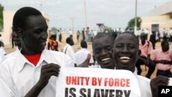 Southern Sudanese men hold a pro-independence poster as they wait for the arrival of envoys from the UN Security Council at the southern Sudanese capital Juba, 6 Oct 2010