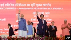 Japanese Prime Minister Shinzo Abe, right and Indian Prime Minister Narendra Modi wave during the ground breaking ceremony for high speed rail project in Ahmadabad, India, Sept. 14, 2017.