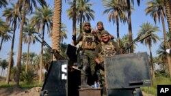 """Soldados iraquíes patrullan Jurf al-Sakhar, 70 kilometros al sur de Bagdad. """"Soldados fantasmas"""" llenan las planillas del ejército de Irak."""