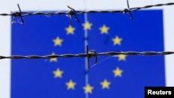Žica ispred zastave Evropske unije u imigracionom centru u Mađarskoj