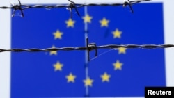 A barbed wire is seen in front of a European Union flag at an immigration reception center in Bicske, Hungary, June 25, 2015.