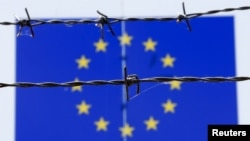 Barbed wire is seen in front of a European Union flag at an immigration reception center in Bicske, Hungary, June 25, 2015.