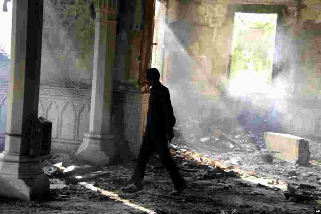 An Egyptian walks among the burned remains of the Rabaah al-Adawiya mosque, in the center of a camp of Morsi supporters that was cleared by security forces, Nasr city, Cairo, August 15, 2013.