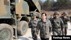 한민구 한국 국방부 장관(가운데)이 28일 최전방에 위치한 북한의 방사포·장사정포 위협을 무력화하는 임무를 띤 다연장로켓 '천무' 운용 부대를 찾아 순시하고 있다.
