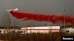 Sebuah pesawat terbang rendah untuk menyemprotkan larutan pemadam api. Fort McMurray, Alberta, Kanada. (Foto: Reuters/Mark Blinch)