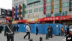 Chinese guards stand at the entrance of the pedestrian Wangfujing area in Beijing. In the background are the blue metal barriers of a construction site that partially blocks the designated spot for anti-government protests, February 25, 2011.