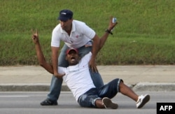 A Cuban dissident is prevented by security personnel from approaching the popemobile as Pope Francis arrives at Revolution Square in Havana, Sept. 20, 2015.