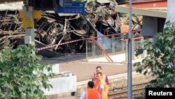 Para petugas tengah berdiri di dekat gerbong kereta yang longsor di stasiun kereta Bretigny-sur-Orge dekat Paris (13/7).