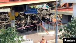 法国铁路官员站在脱轨列车残骸旁边