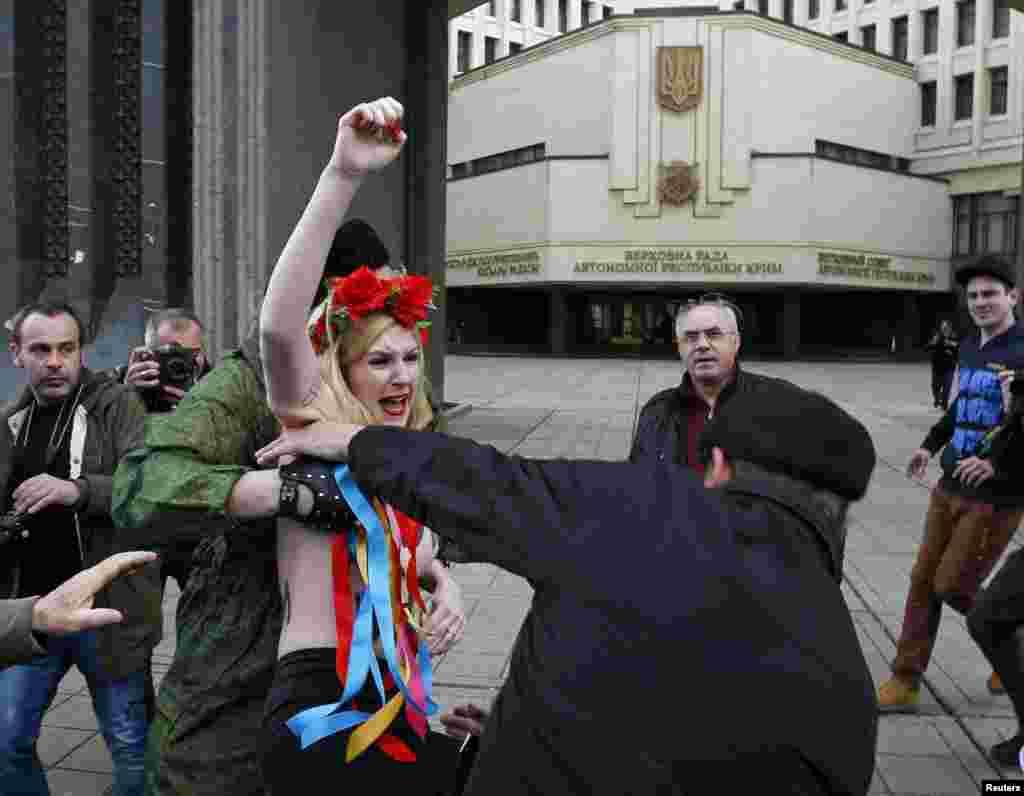 Pripadnici jedinice teritorijalne odbrane na Krimu zaustavljaju pripadnice ukrajinske feminisitičke grupe Femen na protestu ispred parlametarne zgrade u Simferpolu. 6. mart, 2014.