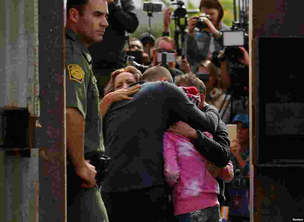 U.S. Border patrol agents stands at an open gate on the fence along the Mexico border as Adrian Gonzalez-Morales and his daughter Aileen hug his parents Juan and Martha, as part of Universal Children's Day at the Border Field State Park, California, Nov. 19, 2016.