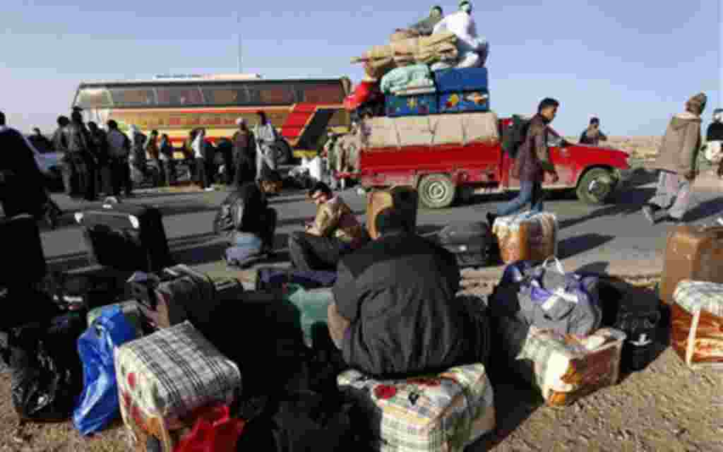 Egyptians who fled from Libya through the Salloum land port gate wait with their belongings at the Egyptian-Libyan border, in Salloum, Egypt, Tuesday, Feb. 22, 2011. An estimated 5,000 Egyptians have returned home from Libya by land, and about 10,000 more
