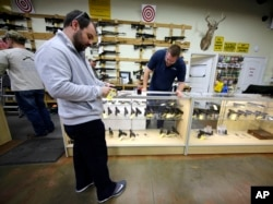 FILE - David Foley, center, looks as a handgun while shopping at the Spring Guns and Ammo store, Jan. 4, 2016, in Spring, Texas.