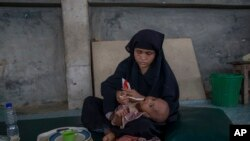A Rohingya Muslim woman, who crossed over from Myanmar into Bangladesh, feeds her daughter inside the centre of Action contre La Faim (ACF) for malnutrition children near Kutupalong, Bangladesh, Sunday, Oct. 22, 2017.