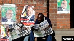 Locals read newspapers in Mbare township, outside Harare August 4, 2013. Africa's oldest president, Robert Mugabe, was declared winner of Zimbabwe's election on Saturday.