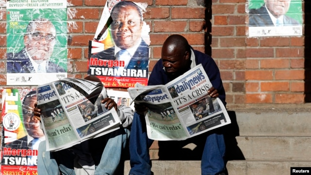 Zimbabweans read newspaper coverage of the recent elections in Mbare township, outside Harare, Zimbabwe, August 4, 2013.