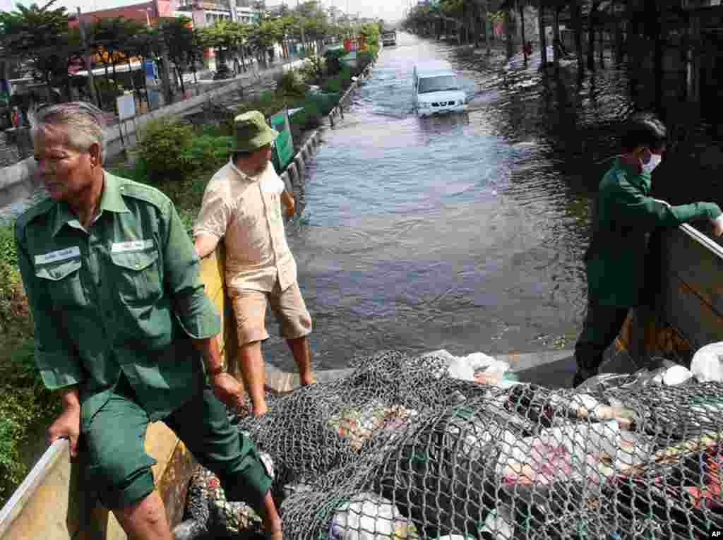 A garbage collection truck ploughs through waist-deep water in Phet Kasem, Bangkok, where waste has been piling up for six days without collection. The truck was full after just two stops, November 9, 2011. (VOA - G. Paluch)
