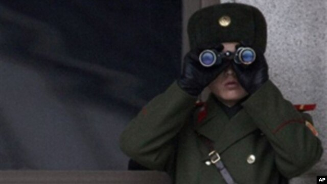 A North Korean soldier looks at the southern side through telescopes at the border village of the Panmunjom, South Korea, Wednesday,  Dec. 8, 2010.