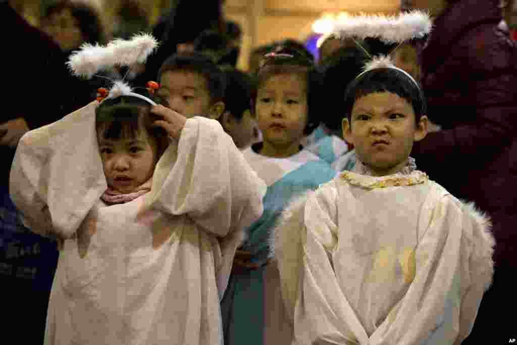 Children dressed as angels take part in a mass on the eve of Christmas at the South Cathedral official Catholic church in Beijing, China.